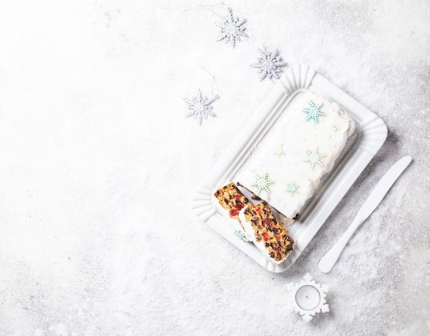 クリスマスフルーツケーキ、雪の背景にプリン。新年のペストリー