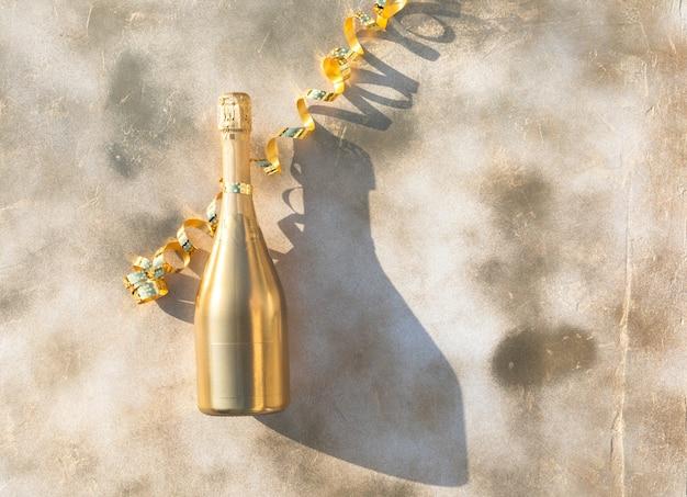 Бутылка золотого шампанского на праздничном фоне.