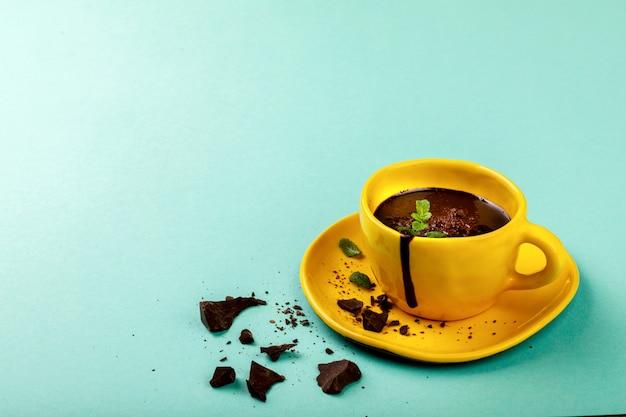 カラフルな背景に黄色のカップドリンクデザートに緑のミントとホットチョコレート