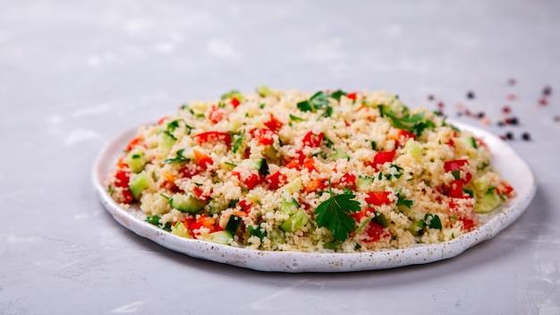 Салат табуле с кус-кусом на тарелке.