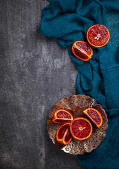 Кровавый апельсин в металлической пластине с ножом