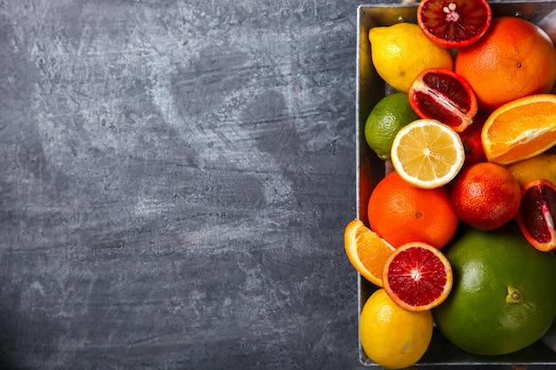 Различные цитрусовые в металлическом подносе. смешанные красочные тропические фрукты