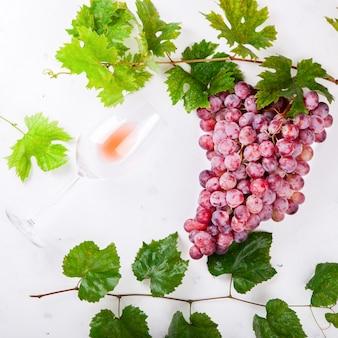Вино розовое и виноградная гроздь. алкогольный напиток