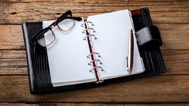 Блокнот с ручкой и очками