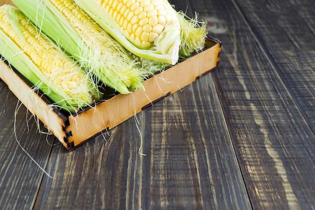 暗い木製のテーブルに緑の葉と新鮮なトウモロコシ。