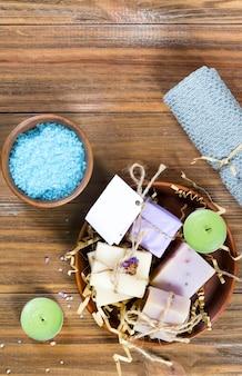 バスケットの自家製有機石鹸とコピースペースを持つ茶色の木製のテーブルの上にボウルに海の塩。