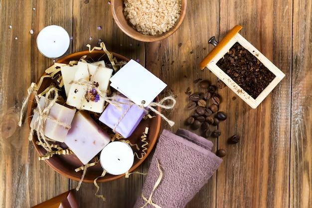 コーヒー豆で飾られた木製の茶色のテーブルの上の天然海塩コーヒー石鹸のセット