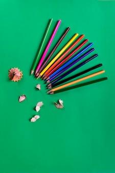 学校は、紙の濃い緑色の背景に鉛筆を着色しました。学用品。平置き