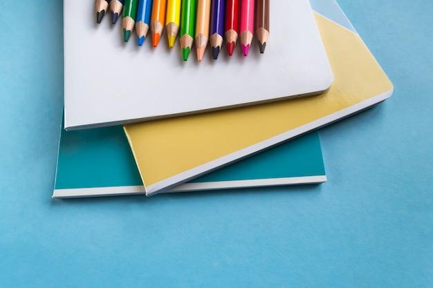 Набор тетрадей и цветных карандашей на зеленом фоне с пространством для текста. школьные принадлежности. плоская планировка