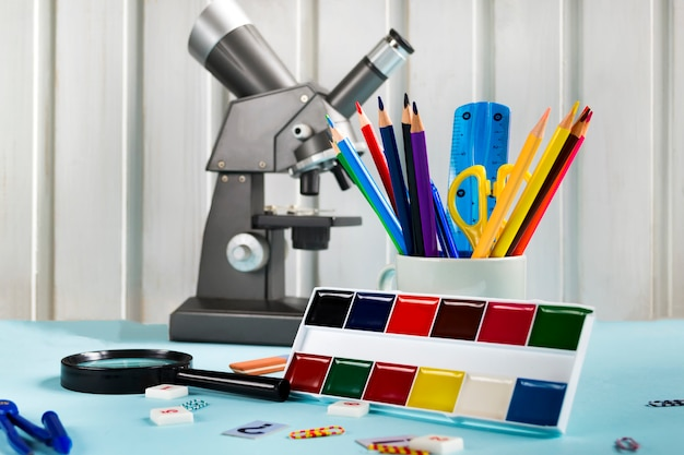 Цветные карандаши, ножницы, линейка, микроскоп, краски на синем фоне. набор школьных принадлежностей, школьные принадлежности