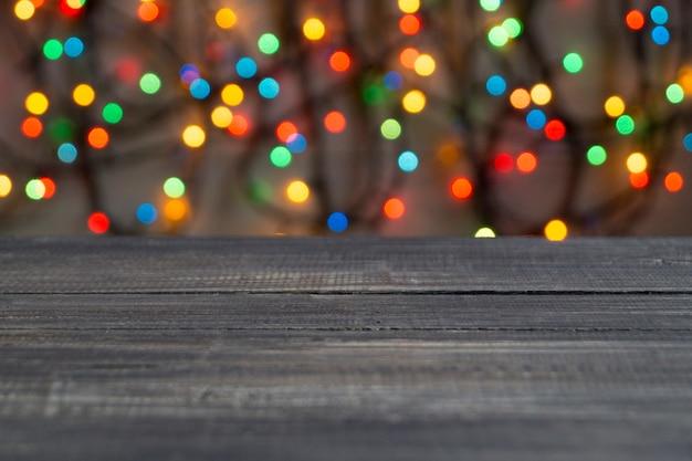 木製の表面の背景に色とりどりのぼやけたライト