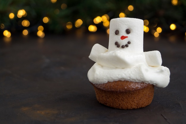 雪だるまの装飾が施されたクリスマスチョコレートカップケーキ。暗い背景に。