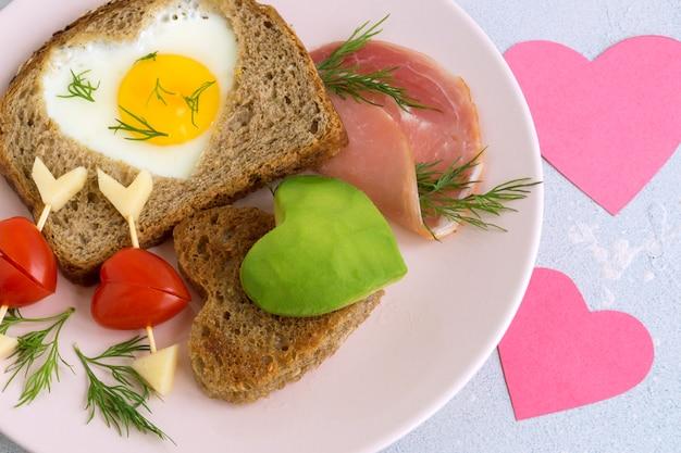 Завтрак на день святого валентина. яйцо и тост в форме сердца.