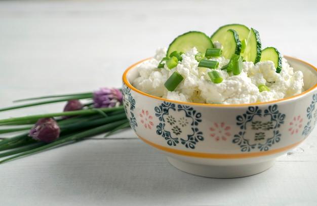 パセリの巻き毛の葉と白いテーブルにカードクリームのボウル。
