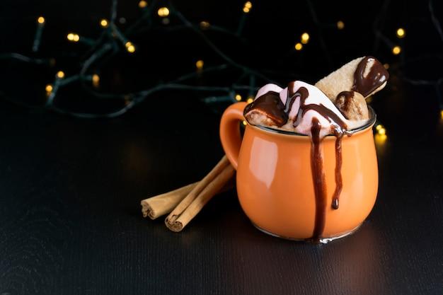黒い背景にオレンジ色のマグカップでココア。