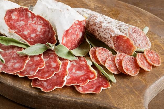 木製の背景にスパイスとフレンチチーズ乾燥サラミのスライス