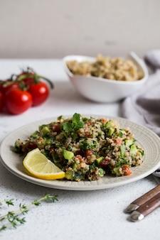 フレッシュトマト、きゅうり、サラダの葉のキノアサラダ。スーパーフードと健康的な食事。