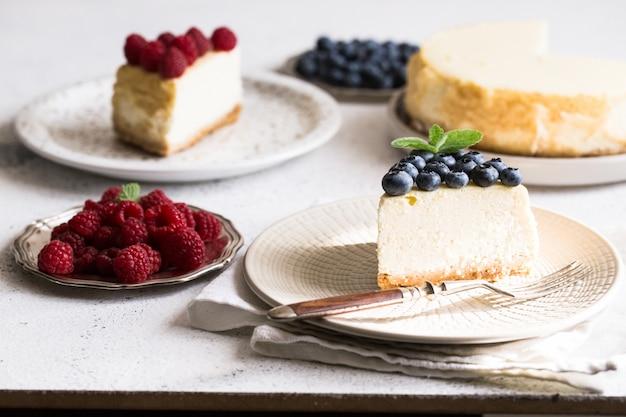 ブルーベリーとラズベリーホワイトプレート上の古典的なニューヨークチーズケーキのスライス。クローズアップビュー。ホームベーカリー