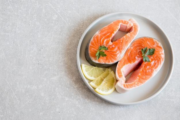 Свежая рыба. свежие стейки из лосося с лимоном в легкой тарелке