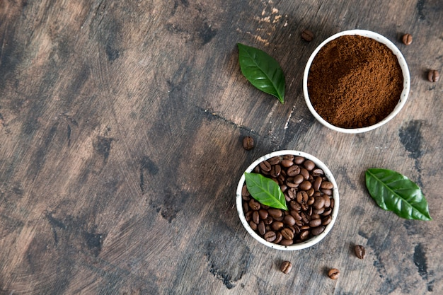 Кофе в зернах и молотый кофе в мисках с листом кофейного дерева на темном