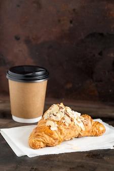 焼きたてのクロワッサンと暗闇の中で紙コップのコーヒー