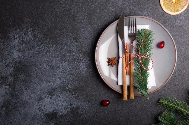 Рождественский стол с тарелкой, вилкой, ножом, еловыми ветками и елочными украшениями.