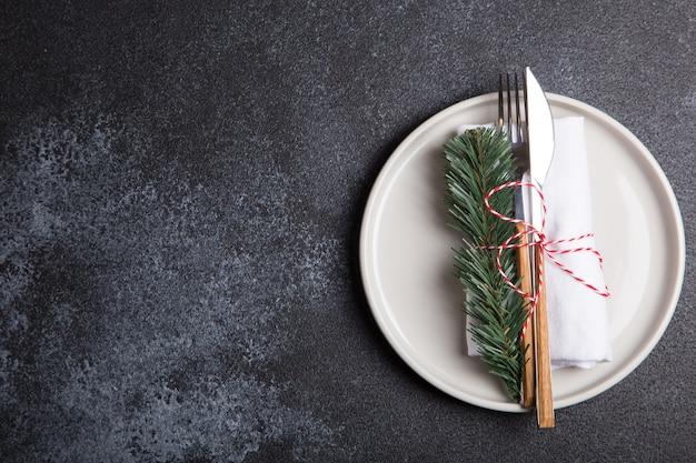 Рождественский стол с тарелкой, вилкой, ножом, еловыми ветками и елочными украшениями. вид сверху, копия пространства