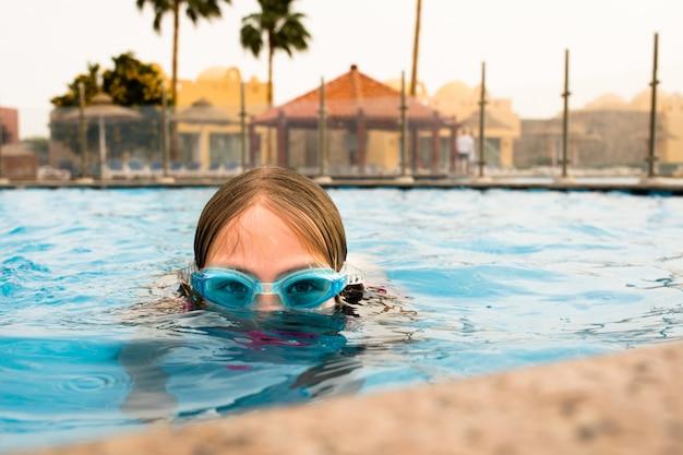 ゴーグル付きのスイミングプールで水中の若い女の子の楽しみ。夏。夏休みの楽しみ