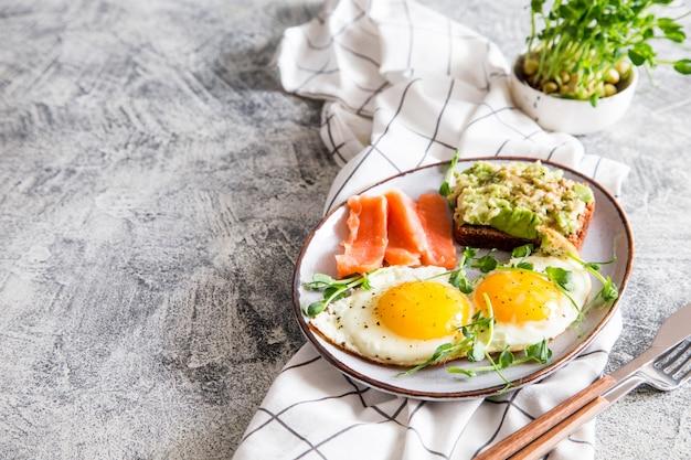 Здоровый питательный завтрак с яйцами, лососем, бутербродом с авокадо и проросшими семенами гороха