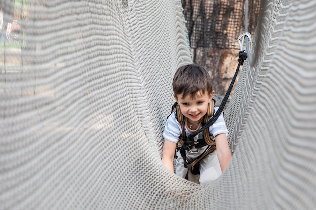 Активный маленький ребенок, играя на альпинистской сети. дети играют и подняться на улице в солнечный летний день.