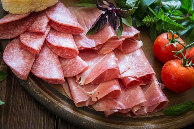 ハム、ブレザオラ、サラミの前菜。パン、トマト、バジル。