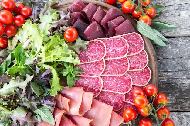 ハム、サラミ、ブレサオラの前菜。トマトとバジル。セレクティブフォーカス