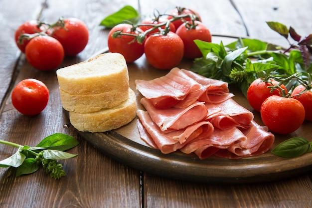 ハムとブレサオラの前菜。トマトとバジル。セレクティブフォーカス
