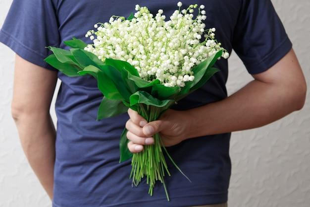 女性のための谷のユリの花束を持った男。男が提案します。