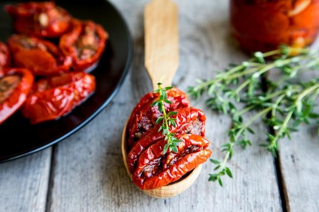 木製の背景に太陽のドライトマトのボウル。ドライトマトとオリーブオイルとハーブ