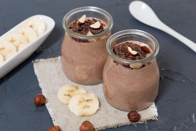 ガラス瓶の中のチアシード、バナナ、ナッツ入りチョコレートプリン