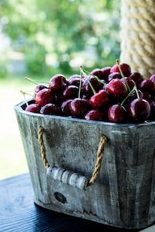 チェリーバスケット桜の木の枝。新鮮な熟したチェリー。庭の甘いチェリー