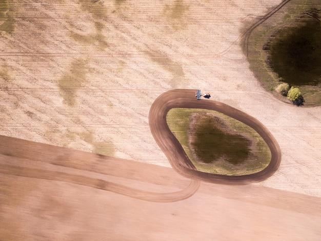 畑、農業分野でのトラクターの空撮。トラクター育成フィールド、空撮