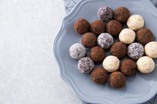 デザートプレートにココアパウダー、ココナッツ、みじん切りヘーゼルナッツのチョコレートトリュフの盛り合わせ