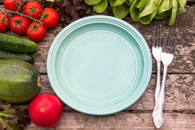 Свежие овощи для вкусной веганской и диетической кулинарии или приготовления салата вокруг пустой тарелки на деревенском деревянном фоне, вид сверху