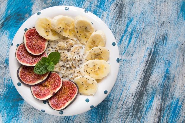 健康的な朝食:新鮮なイチジク、バナナ、ココナッツミルク、チアシードのオートミール