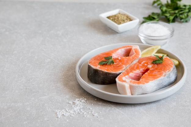 Свежая рыба. свежие стейки из лосося с лимоном, специями и солью в легкой тарелке