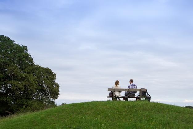 公園のベンチに座っているカップル。ベンチの恋人