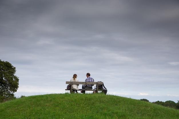 Пара, сидя на скамейке в парке. влюбленные на скамейке