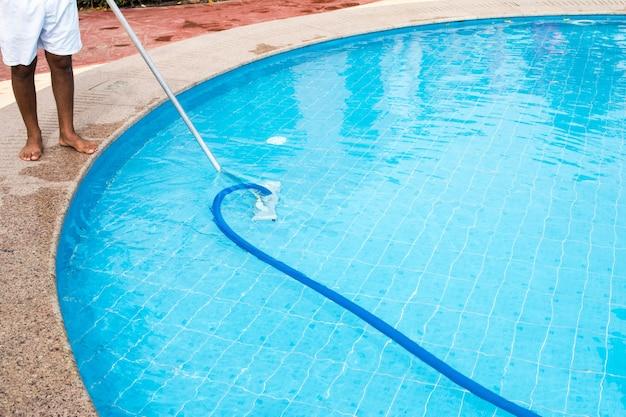 男は夏にプールを掃除します。スイミングプールの掃除機