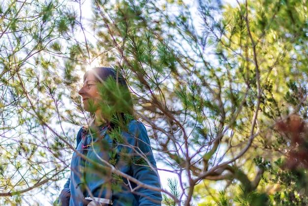 明るい日に植生を歩いているカジュアルな服を着た若い女性の側面図
