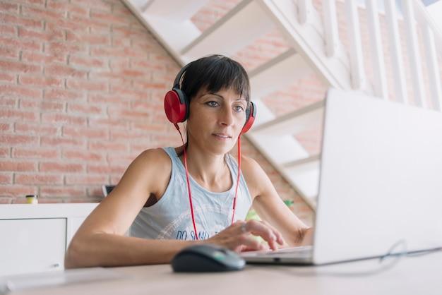 Женщина с ноутбуком, работа на дому во время прослушивания музыки в наушниках