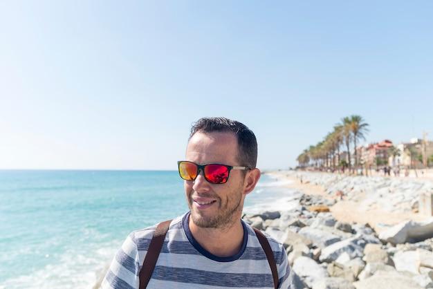 晴れた日に海岸に立っているひげを生やした若者の肖像