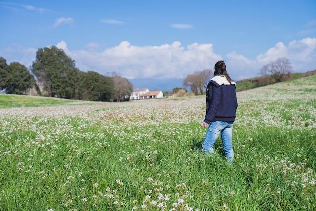 Вид сзади испанская брюнетка женщина в повседневной одежде, ходить на поле