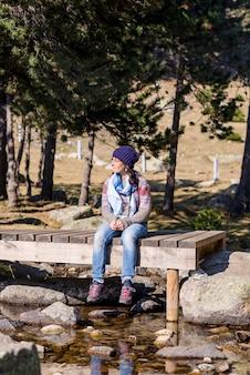森で日光浴をしながらストリーム上の木製の橋の上に座っているウールの帽子の女